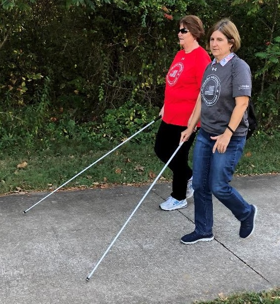 Photo of two blind women, using their white canes are taking a walk in the park.