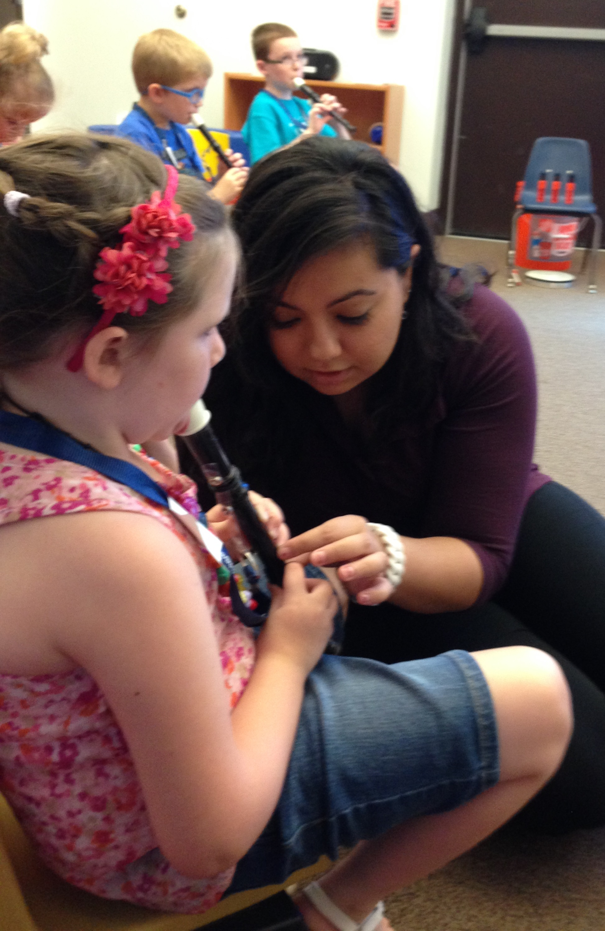 Photo of a blind woman helping teach a young blind girl how to play the recorder with three other blind children in the background playing their recorders.