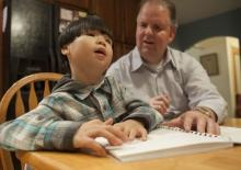 Photo of a blind father teaching his blind son how to read braille.