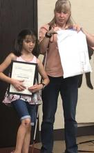 Photo of a blind teacher giving an award to her blind student.